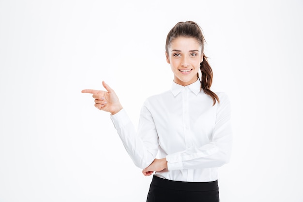 Портрет улыбающейся молодой бизнес-леди, указывая пальцем на белую стену и глядя на фронт