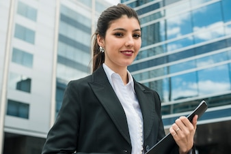 Portrait of a smiling young businesswoman standing in front of building