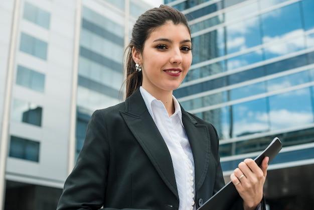 Портрет улыбающегося молодой предприниматель, стоя перед зданием