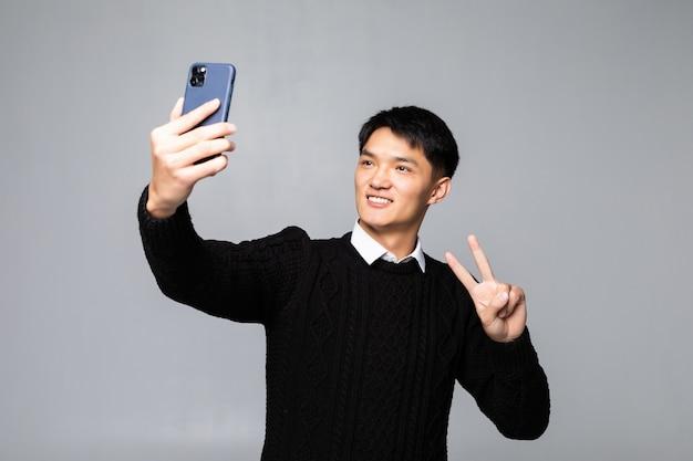 Портрет улыбающегося молодого китайского человека, делающего селфи с мобильным телефоном, в то время как изолированный по белой стене