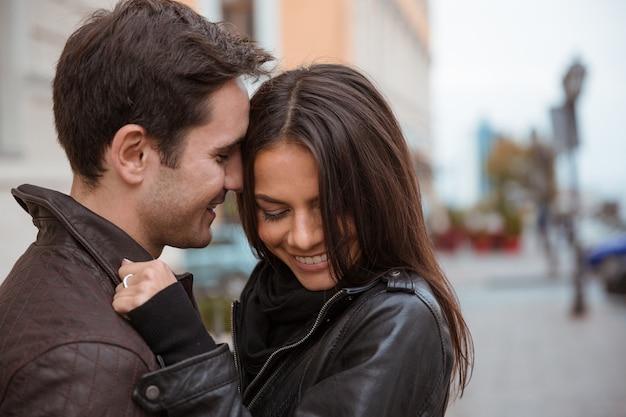 屋外で抱き締める笑顔の若いカップルの肖像画
