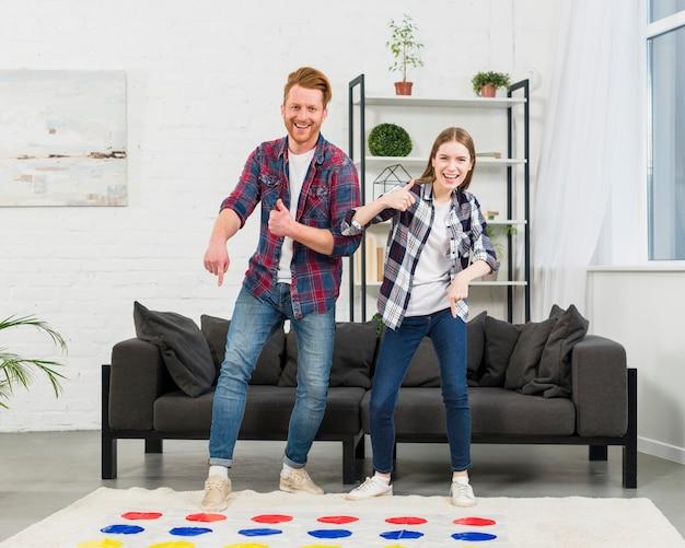 Портрет улыбающегося молодая пара, указывая пальцем на цветную точку игры, показывая пальцем вверх знак