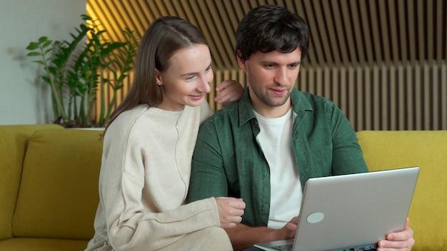 집에서 노란색 소파에 앉아있는 동안 노트북을 사용하는 웃는 젊은 부부의 초상화