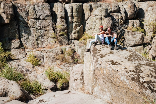 ハイキングでリラックスしたバックパックと笑顔の若いカップルの肖像画