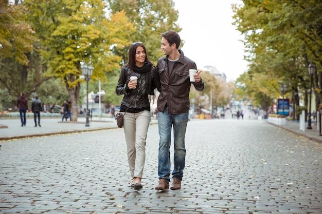古いヨーロッパの街で屋外を歩くコーヒーと笑顔の若いカップルの肖像画