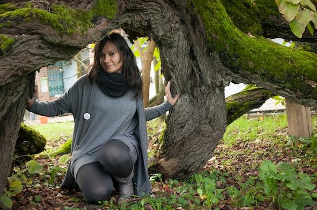 나무 난간 아래에서 무릎을 꿇고 웃고 있는 어린 검은 머리 소녀의 초상화