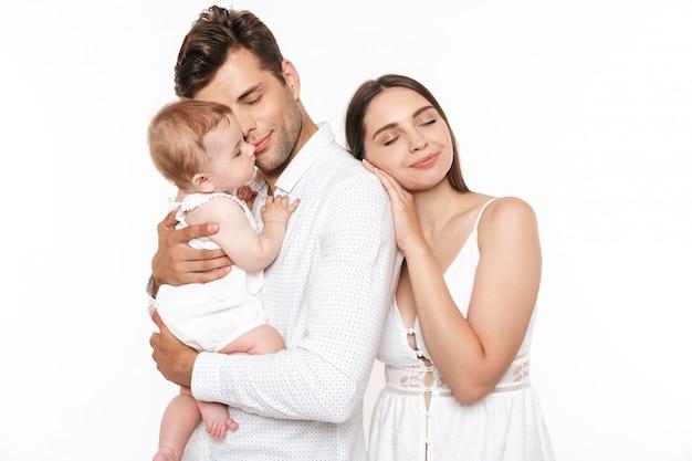 彼らの小さな女の赤ちゃんと笑顔の若い家族の肖像画