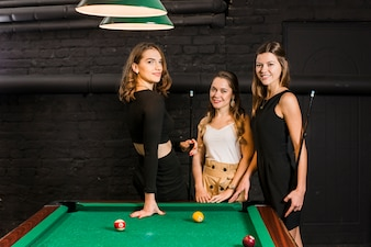 Portrait of a smiling young female friends standing near snooker table