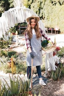 Портрет улыбающегося молодой женщины садовник держит мотыгу и корзина в саду