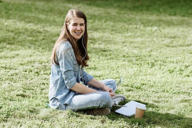 Портрет улыбающейся молодой студентки, сидящей на зеленой траве в парке в летний день