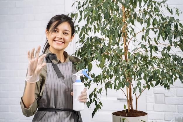 Портрет усмехаясь молодой женщины садовника показывая капсулу с удобрением для комнатного растения. садовая концепция