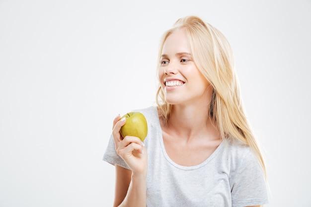 흰 벽에 격리된 녹색 사과를 들고 웃고 있는 어린 소녀의 초상화
