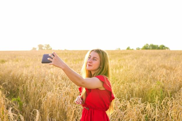 Портрет улыбающейся молодой девушки, делающей селфи фото в поле