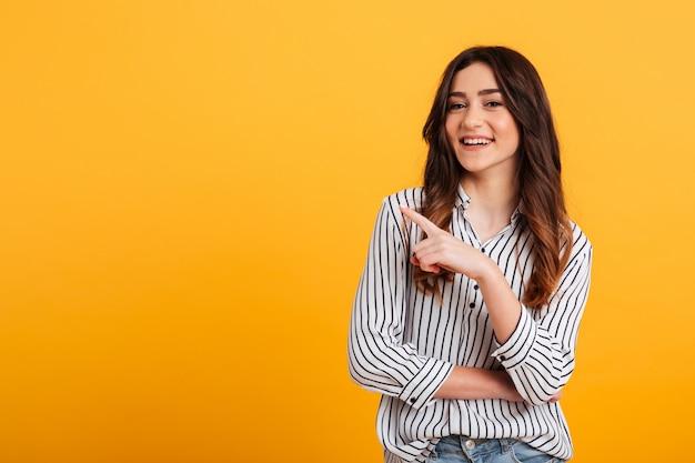 Портрет улыбающегося молодой девушки, указывая пальцем