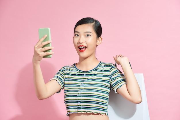 Портрет улыбающейся молодой девушки, стоящей изолированно над розовым, неся сумки и используя мобильный телефон