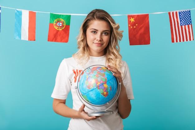 青い壁の上に孤立して立っている、地球儀を保持しているボリューターtシャツを着て笑顔の少女の肖像画