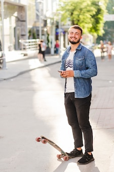 Portrait of a smiling young male skateboarder with mobile phone