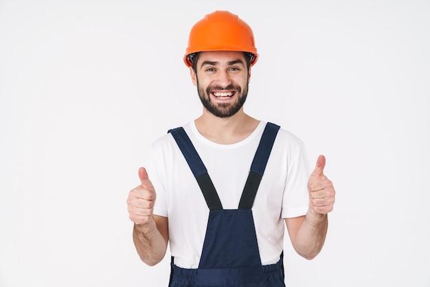 親指を立てるジェスチャーを示す白い壁の上に孤立したポーズのヘルメットの笑顔の若い男のビルダーの肖像画。