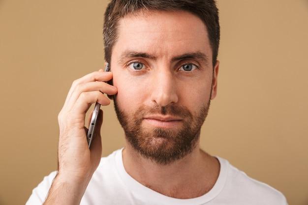 孤立して立って、携帯電話で話しているカジュアルな服を着て笑顔の若い男の肖像画