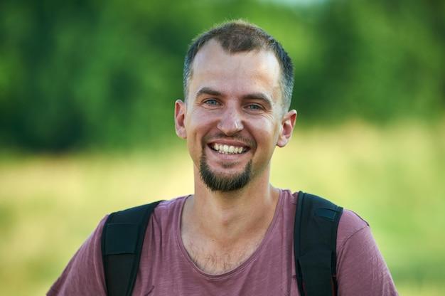 Портрет улыбающегося молодого человека в парке