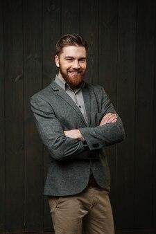 Портрет улыбающегося молодого человека в повседневном костюме, стоящего со сложенными руками, изолированного на черном деревянном фоне