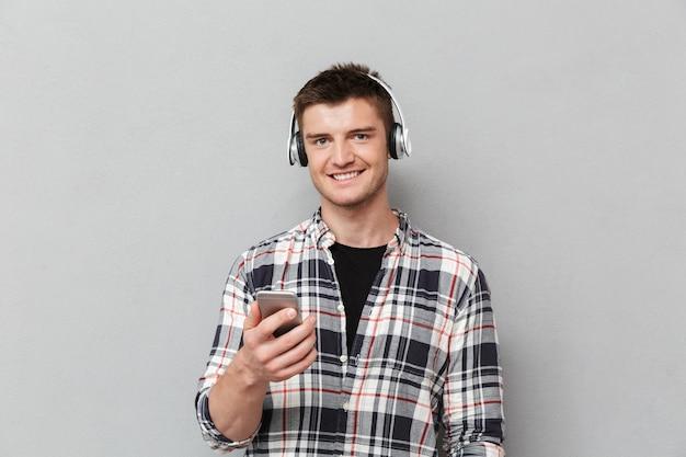 Портрет улыбающегося молодого человека, слушающего
