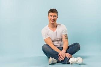 Портрет улыбающегося молодого человека, сидя со скрещенными ногами, глядя на камеру