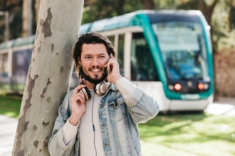 Portrait of a smiling young man talking on mobile phone against blurred bus
