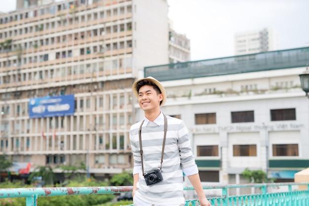 가방을 들고 여행하는 웃고 있는 청년의 초상