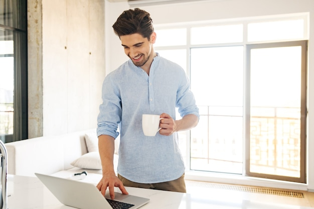 ラップトップコンピューターを使用して笑顔の若い男の肖像画