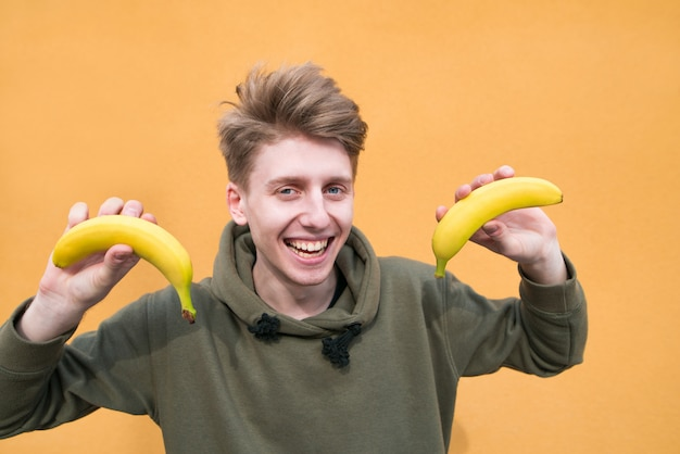 Портрет улыбающегося молодого человека с бананами в руках на оранжевой стене.