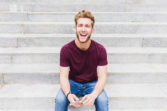 Portrait of a smiling young man with smartphone