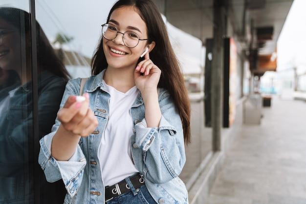 Портрет улыбающегося студента молодой красивой женщины в очках, прогулки на открытом воздухе, отдыха, прослушивания музыки с наушниками.