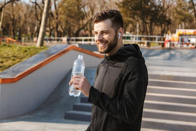 Портрет улыбающегося молодого спортсмена в наушниках