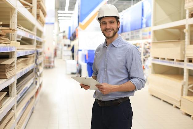 Портрет улыбающегося молодого складского работника, работающего в оптовом магазине за наличные и нести.