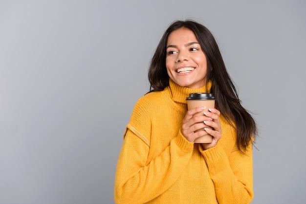 회색 벽 위에 절연 테이크 아웃 커피 컵을 들고 스웨터를 입고 웃는 젊은 여자의 초상화, 멀리보고