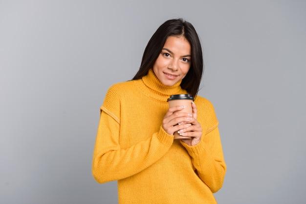 회색 벽 위에 절연 테이크 아웃 커피 컵을 들고 스웨터를 입고 웃는 젊은 여자의 초상화