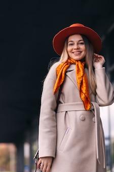 歩行者通りを使用して笑顔の若い女性の帽子の肖像画