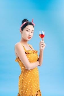 赤ワインのグラスを持った笑顔の若い女性のポートレート