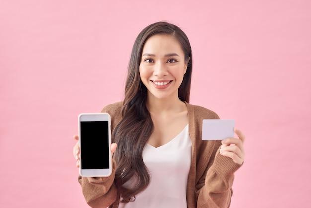 Портрет улыбающейся молодой женщины, держащей пустой экран мобильного телефона, показывая кредитную карту, изолированную на розовом фоне
