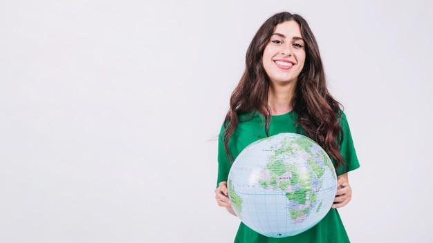 Портрет улыбающейся молодой женщины, держащей глобус