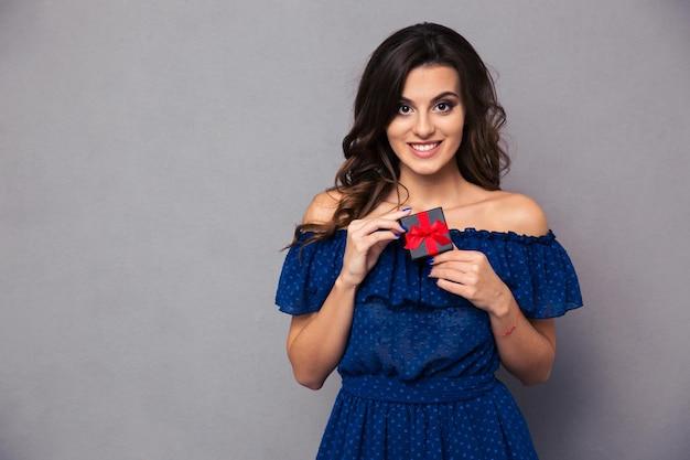 Портрет улыбающейся молодой женщины, держащей подарочную коробку с драгоценностями над серой стеной