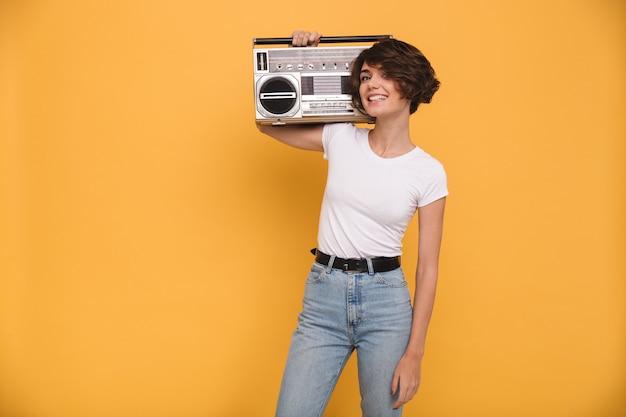 Портрет улыбающейся молодой женщины, держащей проигрыватель