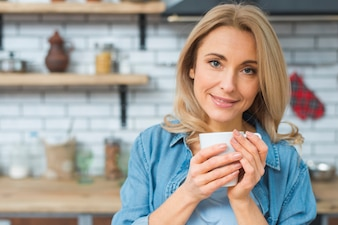 Portrait of a smiling young woman holding white cup of coffee in hand