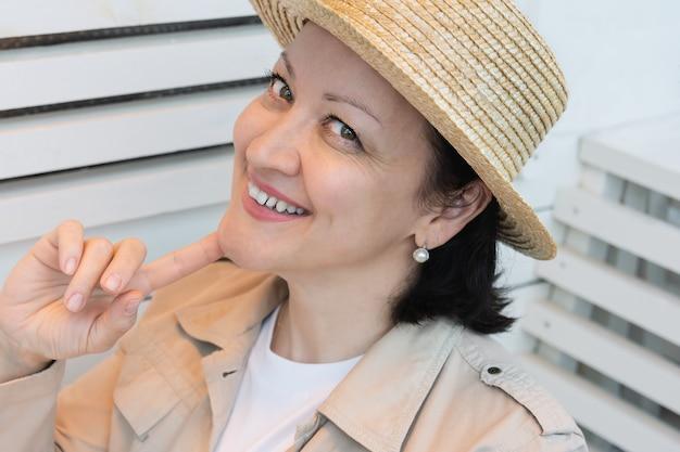 夏服とカフェの夏のテラスに座っている麦わら帽子の笑顔の若い女性の肖像画。