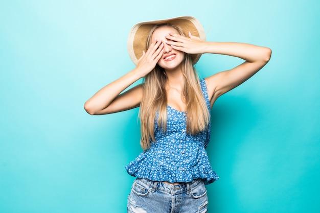 Портрет улыбающейся молодой женщины в летней шляпе, закрывающей глаза руками, изолированными на синем фоне