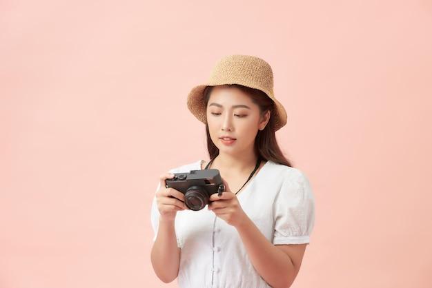 핑크 이상 격리 사진 카메라와 함께 서 여름 모자에 웃는 젊은 여자의 초상화