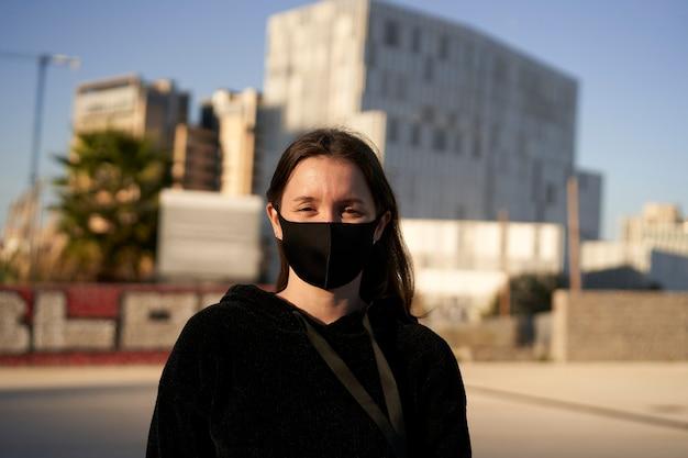 코로나 바이러스 전염병으로 인해 전면을보고 마스크를 쓰고 웃는 젊은 여자의 초상화