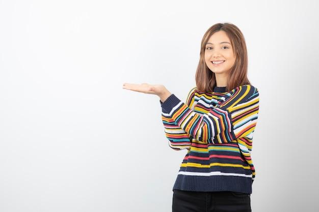 開いた手のひらを示す笑顔の若い女性モデルの肖像画。
