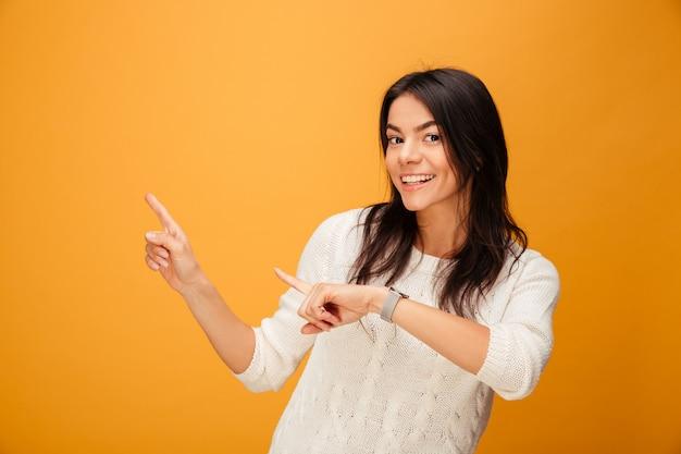 Портрет улыбающегося молодой женщины, указывая пальцами